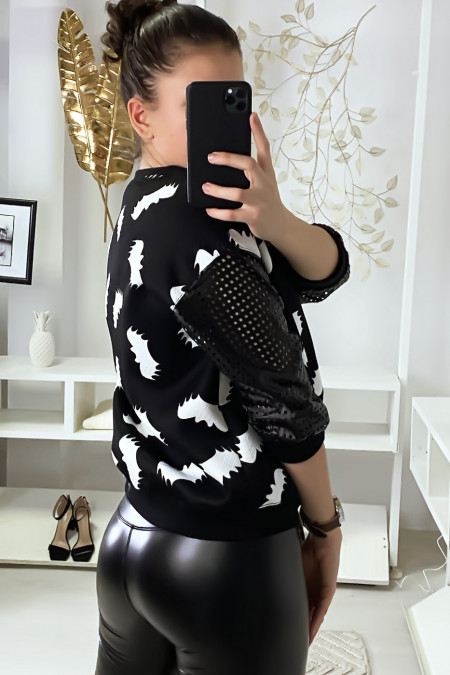 Black sweater with bat motif and sleeves with checkered holes.