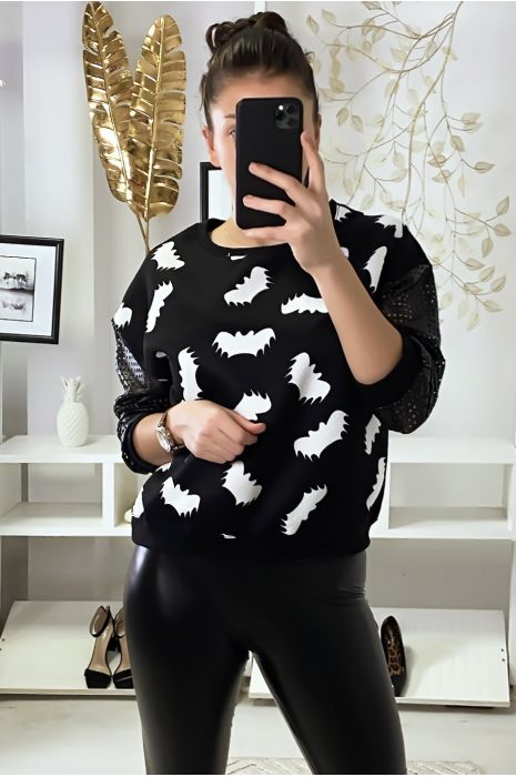Zwarte sweater met vleermuismotief en mouwen met geruite gaatjes.