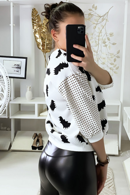 White sweater with bat motif and sleeves with checkered holes.