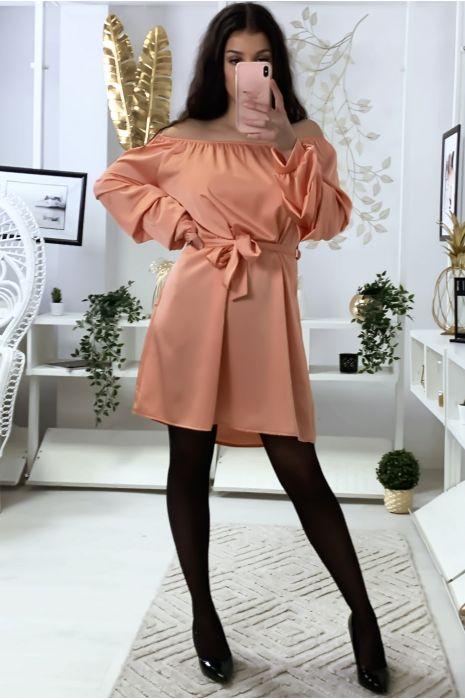 Een koraalkleurige jurk van satijn met boothals, riem en gerimpelde mouwen