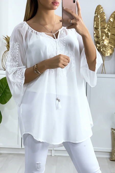 Witte sluiertuniek met mooie borduursels op de kraag en mouwen