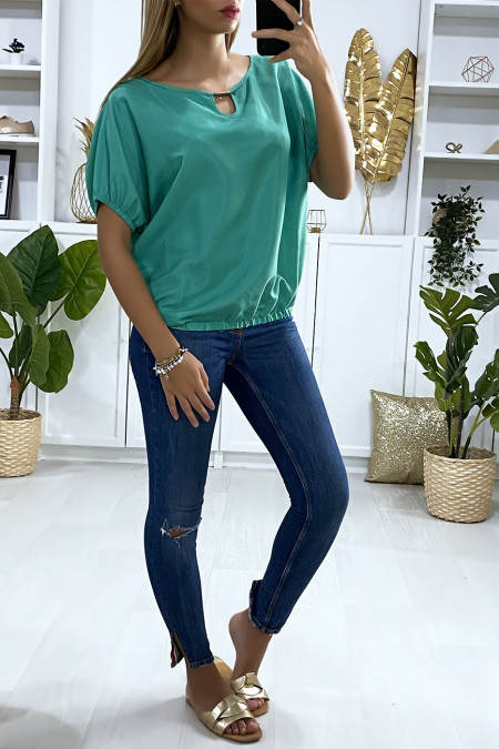Green batwing blouse with elastic and gold accessory at the collar