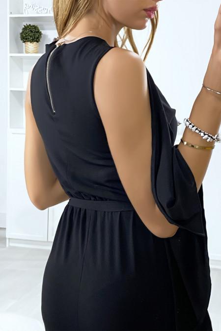 Lange zwarte jurk met ruches aan één mouw en gouden accessoire op de kraag