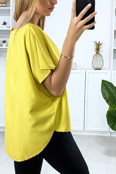 Mosterdkleurige blouse met vleermuismouwen met gouden accessoire bij de kraag