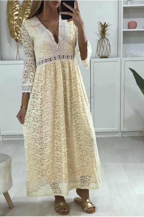 Lange beige kanten jurk met borduursels bij de kraag en taille