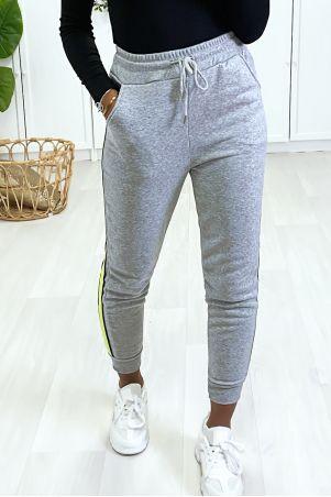 Grijze joggingbroek met fluogele streep aan de zijkant.